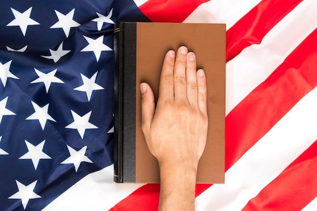 Bovenaanzicht hand op boek en amerikaanse vlag