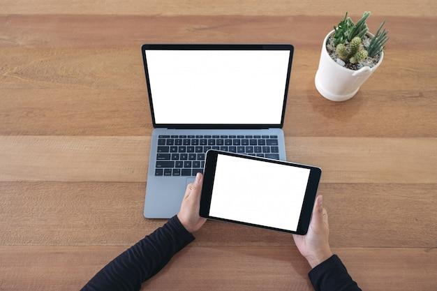 Bovenaanzicht handen met een zwarte tablet en laptop met leeg wit scherm op houten tafel in kantoor