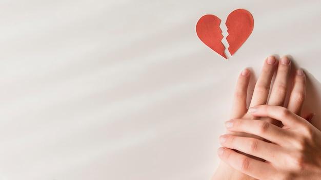 Bovenaanzicht handen met gebroken hart