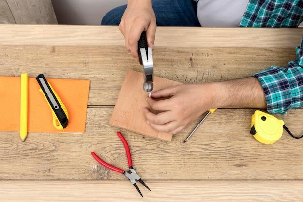 Bovenaanzicht handen met hamer en spijkers