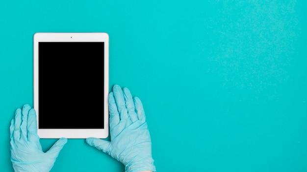 Bovenaanzicht handen met tablet op tafel