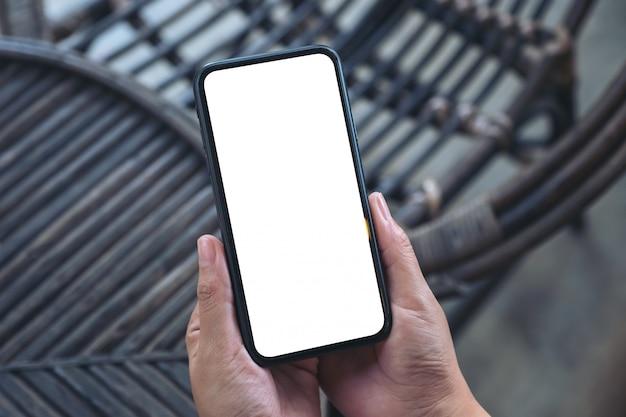 Bovenaanzicht handen met zwarte mobiele telefoon met leeg wit scherm in de buitenlucht