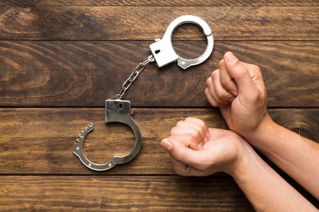 Bovenaanzicht handen pleiten schuldig met handboeien