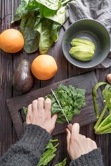 Bovenaanzicht handen snijden salade