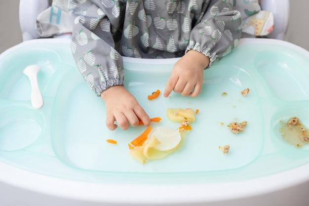 Bovenaanzicht handen van baby zittend op eettafel eten zelf voedsel, baby-led weaning concept