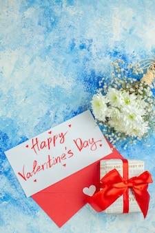 Bovenaanzicht happy valentijnsdag geschreven op brief bloemen rode envelop cadeau op blauwe achtergrond