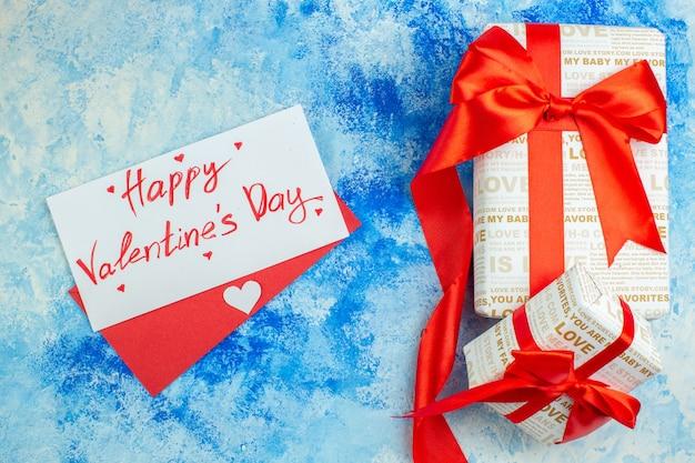 Bovenaanzicht happy valentijnsdag geschreven op brief rode envelop geschenken op blauwe achtergrond
