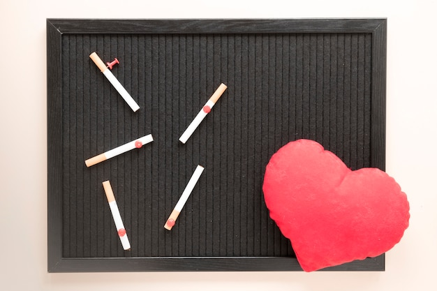 Bovenaanzicht hart en sigaretten op schoolbord