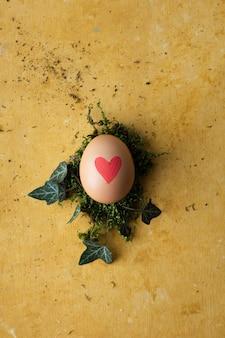 Bovenaanzicht hart geschilderd ei op de tafel