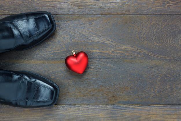 Bovenaanzicht hartvorm met herenschoenen op houten achtergrond met kopie ruimte.
