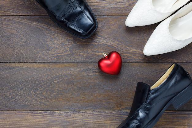 Bovenaanzicht hartvorm met mannen schoenen en vrouwen schoenen op houten achtergrond.