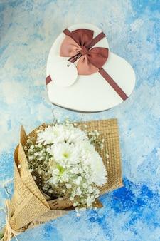 Bovenaanzicht hartvormige doos bloemen op blauwe achtergrond