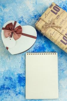 Bovenaanzicht hartvormige doos geschenk spiraal notebook op blauwe achtergrond