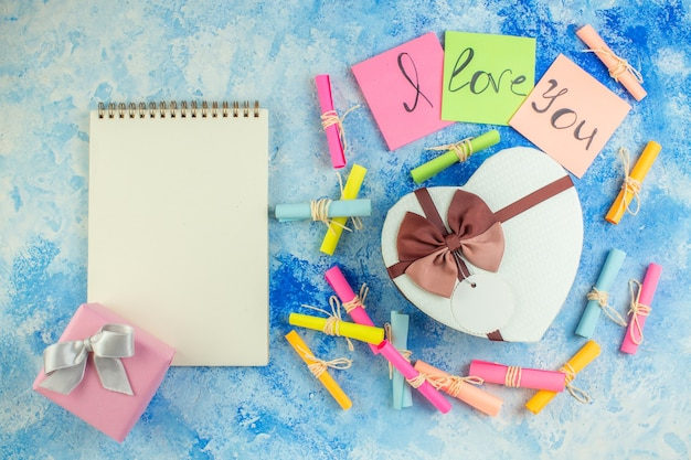 Bovenaanzicht hartvormige doos ik hou van je geschreven op plaknotities scroll wens papieren notitieblok op blauwe achtergrond