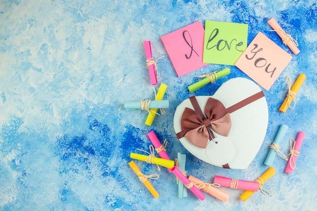 Bovenaanzicht hartvormige doos ik hou van je geschreven op plaknotities scroll wenspapieren op blauwe achtergrond vrije ruimte