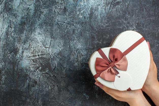 Bovenaanzicht hartvormige doos in vrouwelijke handen op donkere achtergrond kopie plaats