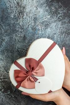 Bovenaanzicht hartvormige doos in vrouwelijke handen op donkere achtergrond