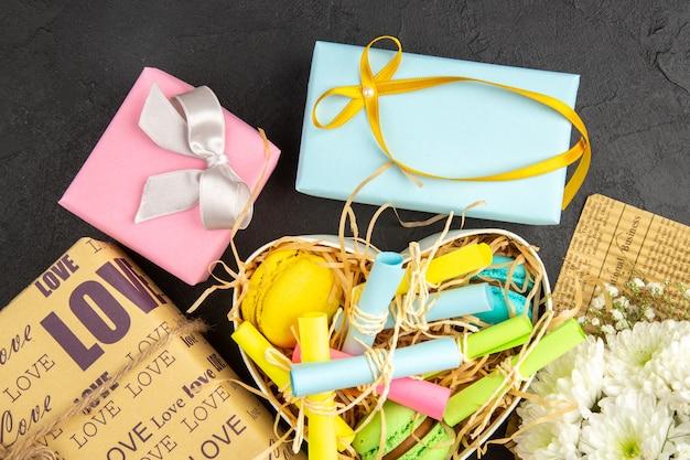Bovenaanzicht hartvormige doos met opgerolde plaknotities en macarons verpakte geschenken bloemboeket op donkere achtergrond