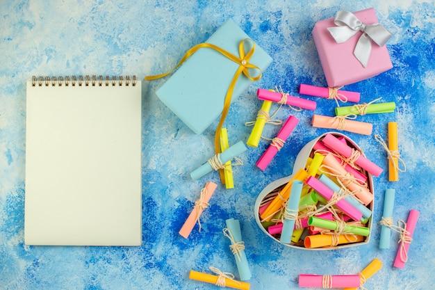 Bovenaanzicht hartvormige doos met scroll wens papieren geschenken notebook op blauwe achtergrond