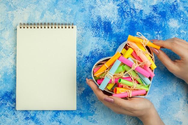 Bovenaanzicht hartvormige doos met scroll-wenspapieren in vrouwenhanden notitieboekje op blauwe achtergrond