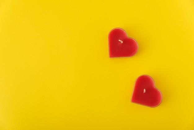 Bovenaanzicht hartvormige kaarsen op gele achtergrond. kopieer ruimte