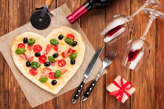 Bovenaanzicht hartvormige pizza met wijn en cadeau