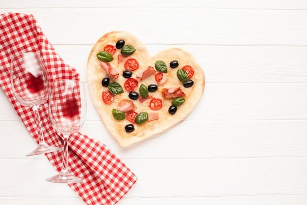 Bovenaanzicht hartvormige pizza op tafel met doek