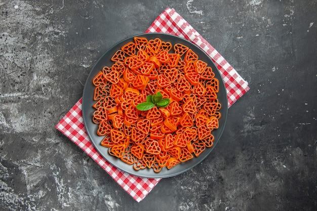 Bovenaanzicht hartvormige rode italiaanse pasta op zwarte ovale plaat op keukenhanddoek op donkere tafel kopieerruimte