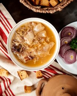 Bovenaanzicht hash traditionele azerbeidzjaanse schotel in een kyasa bord met uien en crackers