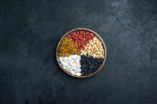Bovenaanzicht hazelnoten en rozijnen en andere noten op de donkergrijze achtergrondfoto van het notenhapje droog fruit