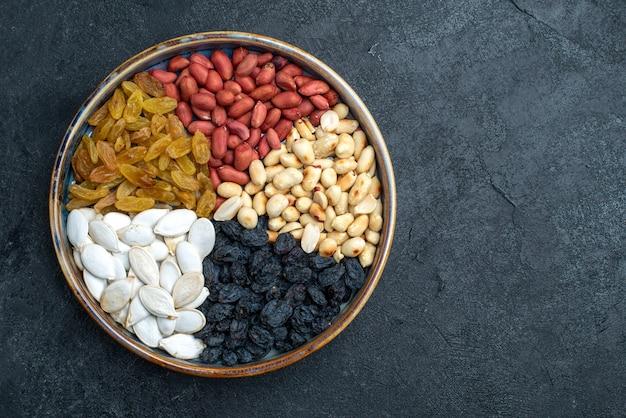 Bovenaanzicht hazelnoten en rozijnen en andere noten op donkergrijze achtergrond noten snack droog fruit foto