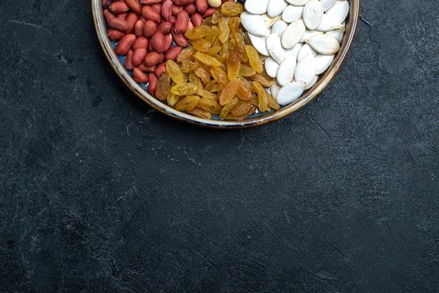 Bovenaanzicht hazelnoten en rozijnen en andere noten op donkergrijze achtergrond noten snack droog fruit