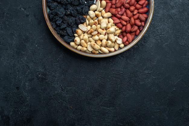 Bovenaanzicht hazelnoten en rozijnen en andere noten op donkergrijze achtergrond notensnack droog fruit