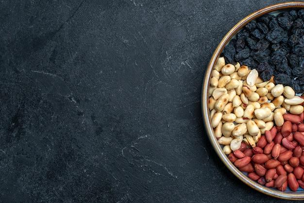 Bovenaanzicht hazelnoten en rozijnen en andere noten op donkergrijze tafelnoot snack droog fruit foto