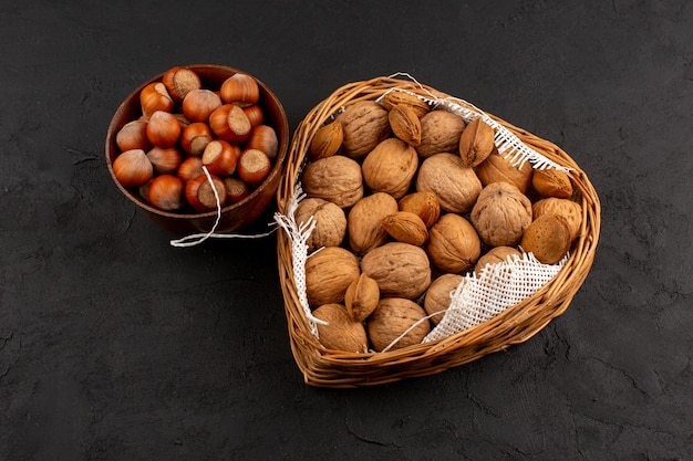 Bovenaanzicht hazelnoten en walnoten in bruine pot en mand op de grijze