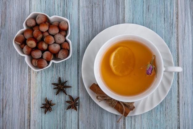Bovenaanzicht hazelnoten in een kom met een kopje thee en een schijfje citroen met kaneel op een grijze achtergrond