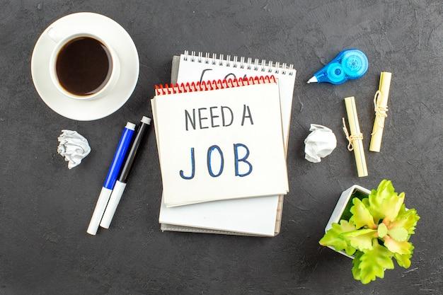 Bovenaanzicht heb een baan nodig geschreven op notitieblok blauwe en zwarte markeringen notitiepapier kopje thee op zwart