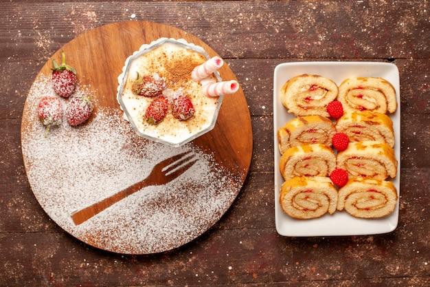 Bovenaanzicht heerlijk aardbeidessert met zoete fruitbroodjes op bruin houten bureau