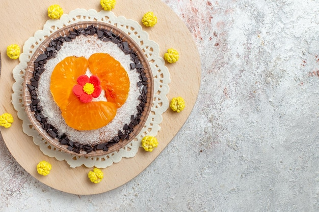 Bovenaanzicht heerlijk cakedessert met gesneden mandarijnen op een witte achtergrond, fruitcake, biscuitdessertroom