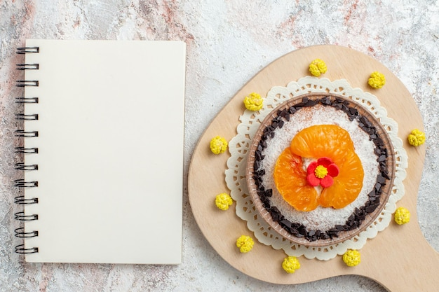 Bovenaanzicht heerlijk cakedessert met gesneden mandarijnen op een witte achtergrond, fruitdessert, biscuitroomcake