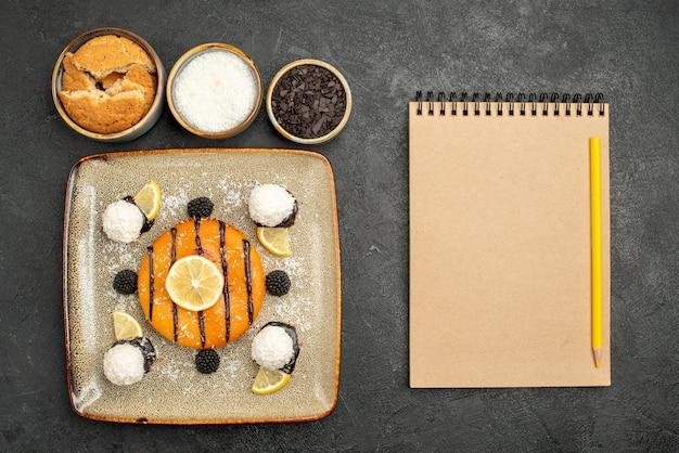 Bovenaanzicht heerlijk cakedessert met kokossnoepjes op donkere oppervlakte caketaartdessert zoete snoepthee