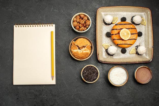 Bovenaanzicht heerlijk cakedessert met kokossnoepjes op donkere oppervlaktecaketaart, zoet snoeptheedessert