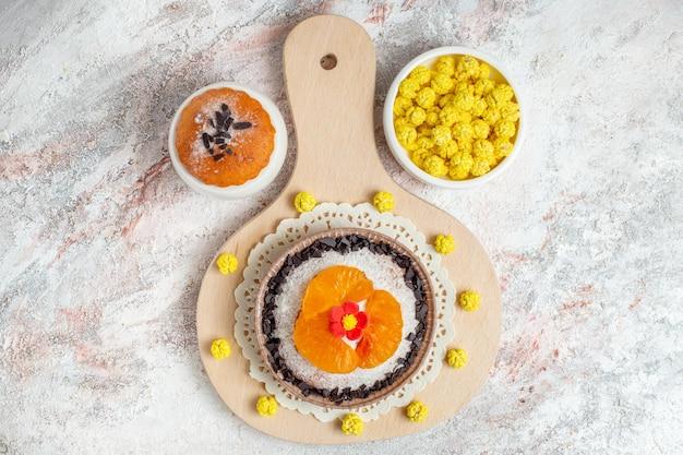 Bovenaanzicht heerlijk chocoladedessert met gesneden mandarijnen op witte achtergrond dessert biscuit cream cake fruit