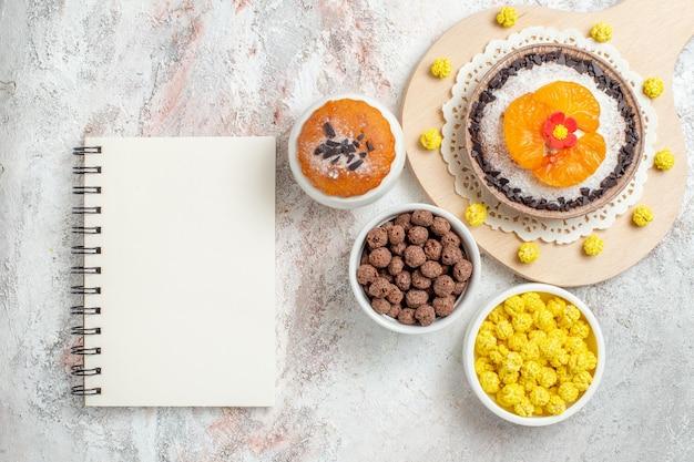Bovenaanzicht heerlijk chocoladedessert met mandarijnen en snoepjes op witte achtergrond crème dessert biscuit cake fruit