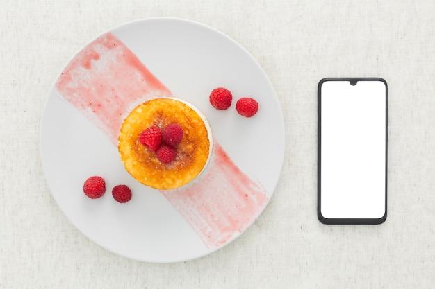 Bovenaanzicht heerlijk dessert en mobiele telefoon