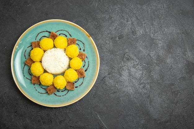 Bovenaanzicht heerlijk dessert kleine gele snoepjes met cake in plaat op de grijze achtergrond snoep thee suiker cake sweet