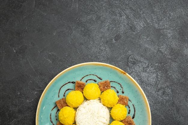Bovenaanzicht heerlijk dessert kleine gele snoepjes met cake in plaat op donkergrijze achtergrond snoep thee suiker cake zoet