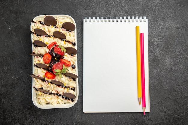 Bovenaanzicht heerlijk dessert met chocoladekoekjes en aardbeien op donkere achtergrond, notenkoekje, zoete fruitkoekjessuiker