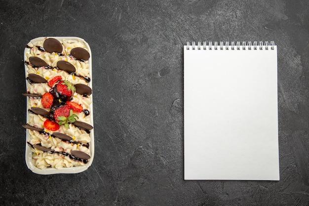 Bovenaanzicht heerlijk dessert met chocoladekoekjes en aardbeien op donkere achtergrond, notenkoekje, zoete vruchten, bessenkoekje