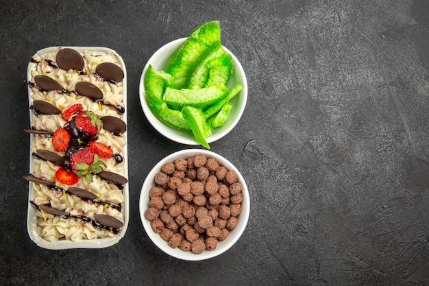 Bovenaanzicht heerlijk dessert met chocoladekoekjes en aardbeien op een donkere achtergrond, notenkoekje, zoete fruitbessenkoekje